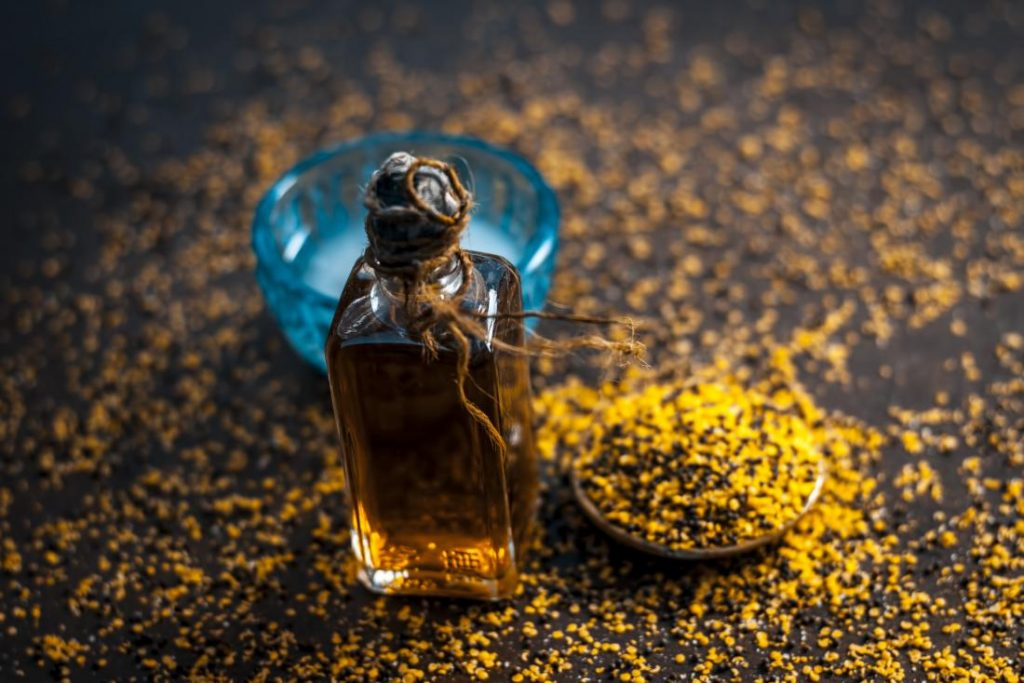 mustard seed oil in glass jar surrounded by mustard seeds on table